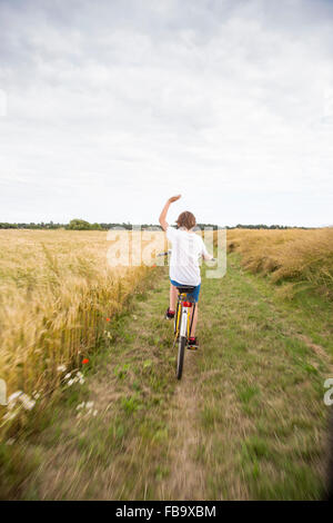 Sweden, Skane, Soderslatt, Beddinge, Boy (12-13) riding bike in wheat field - Stock Photo