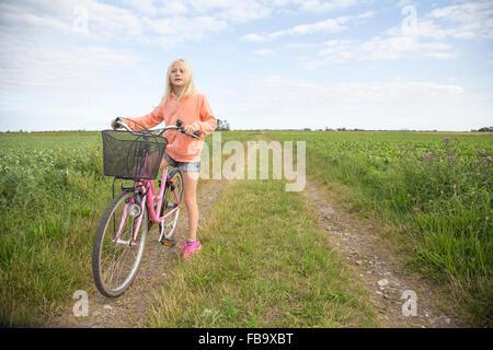 Sweden, Skane, Soderslatt, Beddinge, Blonde girl (10-11) standing with bike on dirt road in green field - Stock Photo