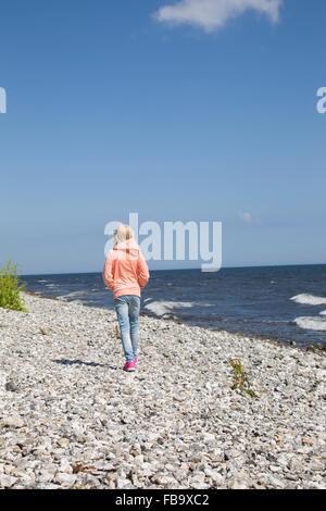 Sweden, Skane, Soderslatt, Smygehuk, Blonde girl (10-11) walking on pebble beach along sea - Stock Photo