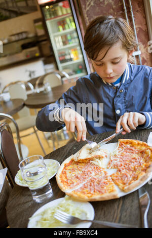Sweden, Boy (12-13) eating pizza in cafe - Stock Photo