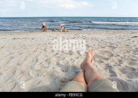 Sweden, Skane, Soderslatt, Beddinge, Father with daughter (10-11) and son (12-13) on beach - Stock Photo