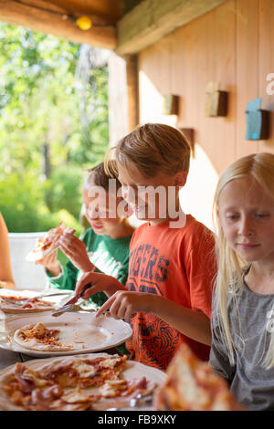 Sweden, Skane, Brothers (8-9) and sister (10-11) eating pizza at family dinner - Stock Photo
