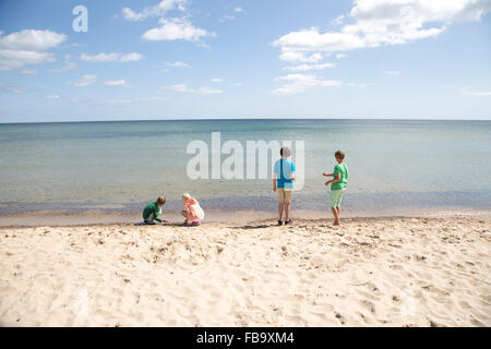 Sweden, Skane, Osterlen, Stenshuvud, Kids (8-9, 10-11, 12-13) playing on beach - Stock Photo