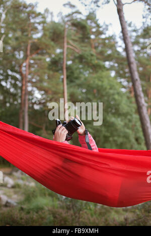 Sweden, Vastergotland, Lerum, Girl (10-11) lying in hammock and taking pictures with camera - Stock Photo