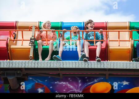 Sweden, Skane, Simrishamn, Excited children (10-11, 12-13) in amusement park - Stock Photo