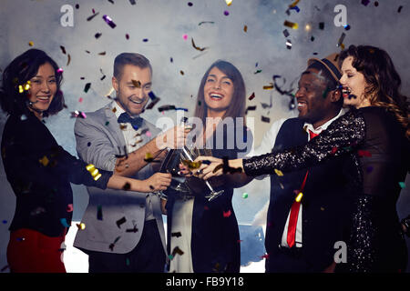 Cheerful friends toasting with champagne at New Year's Eve party - Stock Photo