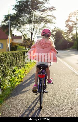 Sweden, Vastergotland, Lerum, Girl (10-11) wearing pink helmet riding bicycle along street - Stock Photo