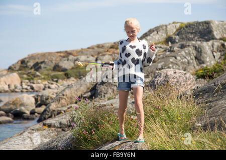 Sweden, Vastergotland, Lerum, Blonde girl (10-11) with fishing rod toy on rock - Stock Photo