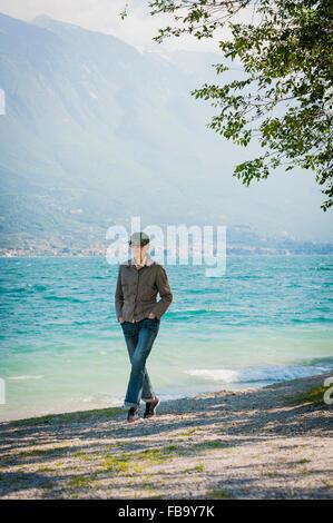 Italy, Lake Garda, Woman walking on lakeshore - Stock Photo