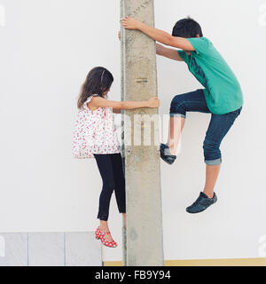 Portugal, Boy (10-11) and girl (6-7) climbing post - Stock Photo