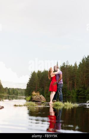 Sweden, Vastmanland, Bergslagen, Svartalven, Mid adult couple kissing - Stock Photo