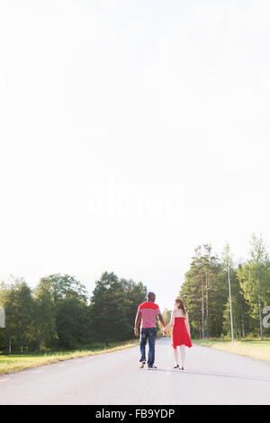 Sweden, Vastmanland, Bergslagen, Hallefors, Rear view of mid adult couple walking on rural road - Stock Photo