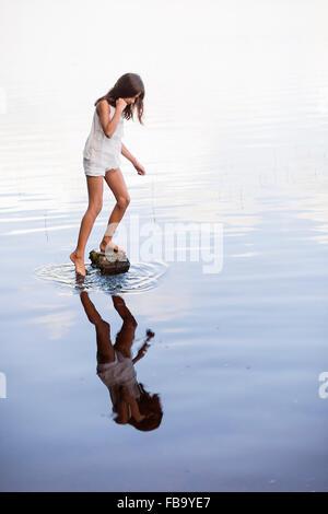 Sweden, Vastmanland, Bergslagen, Svartalven, Girl (8-9) standing on rock in river - Stock Photo