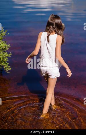 Sweden, Vastmanland, Bergslagen, Svartalven, Rear view of girl (8-9) wading in river - Stock Photo