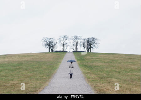 Sweden, Sodermanland, Stockholm, Skogskyrkogarden, Woman at Woodland Cemetery - Stock Photo