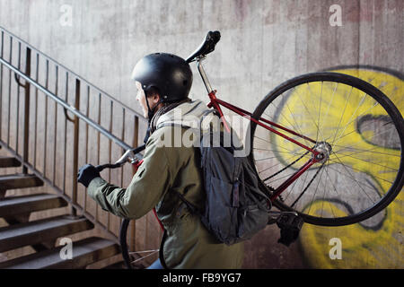Sweden, Sodermanland, Stockholm, Sodermalm, Slussen, Mid adult man carrying bicycle upstairs - Stock Photo