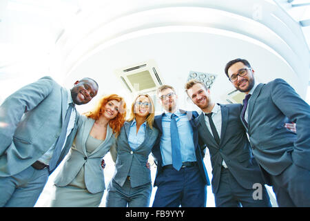 Smiling business team standing together in a row and embracing - Stock Photo