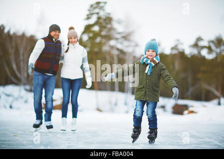 Happy kid on skates in outdoor rink with his parents behind - Stock Photo