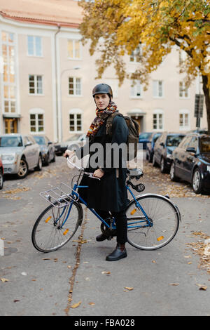 Sweden, Uppland, Stockholm, Vasastan, Rodabergsbrinken, Young man standing with bicycle - Stock Photo