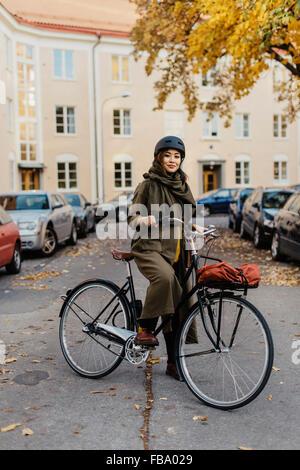 Sweden, Uppland, Stockholm, Vasastan, Rodabergsbrinken, Young woman standing with bicycle - Stock Photo