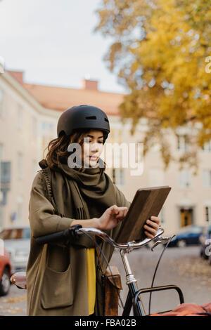 Sweden, Uppland, Stockholm, Vasastan, Rodabergsbrinken, Young woman using digital tablet standing by bicycle - Stock Photo