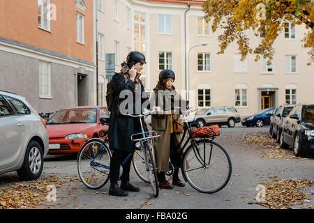 Sweden, Uppland, Stockholm, Vasastan, Rodabergsbrinken, Two people standing with bicycles outdoors - Stock Photo