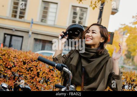 Sweden, Uppland, Stockholm, Vasastan, Rodabergsbrinken, Young woman taking off protective helmet - Stock Photo