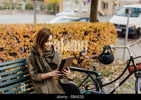 Sweden, Uppland, Stockholm, Vasastan, Rodabergsbrinken, Young woman sitting on bench using tablet - Stock Photo