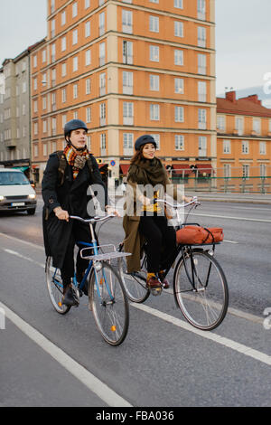 Sweden, Uppland, Stockholm, Vasatan, Sankt Eriksgatan, Man and woman cycling on city street - Stock Photo