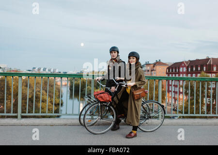 Sweden, Uppland, Stockholm, Vasatan, Sankt Eriksgatan, Young couple with bicycles on street - Stock Photo
