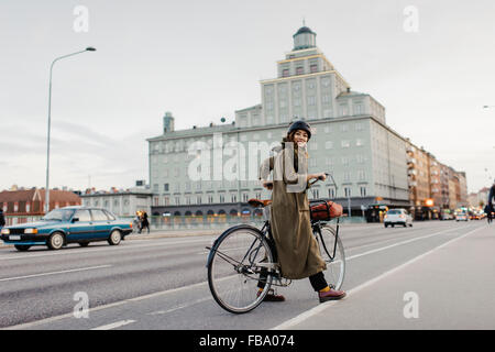 Sweden, Uppland, Stockholm, Vasatan, Sankt Eriksgatan, Woman cycling on city street - Stock Photo