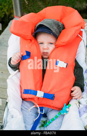 Sweden, Portrait of baby boy (6-11 months) in life jacket - Stock Photo