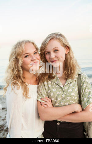 Sweden, Blekinge, Hallevik, Portrait of two teenage girls (14-15, 16-17) at bay - Stock Photo