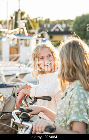 Sweden, Blekinge, Hallevik, Two teenage girls(14-15, 16-17) with bicycles at marina bay - Stock Photo