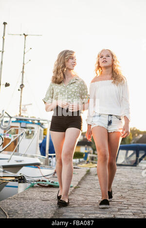 Sweden, Blekinge, Hallevik, Two teenage girls(14-15, 16-17) walking at marina bay - Stock Photo