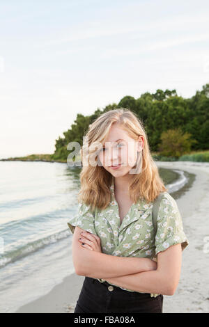 Sweden, Blekinge, Hallevik, Portrait of teenage girl (16-17) standing on beach - Stock Photo