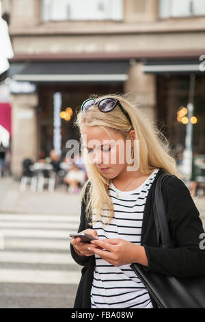 Sweden, Skane, Malmo, Teenage girl (14-15) using smart phone on street - Stock Photo