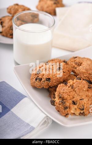 Still life of oatmeal raisin cookies and milk glass - Stock Photo