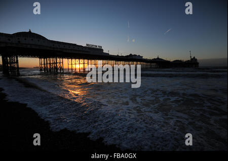 Brighton Pier is silhouetted against a beautiful sunrise on the beach in Brighton, East Sussex, UK. - Stock Photo