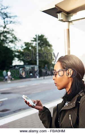 Sweden, Vastra Gotaland, Gothenburg, Woman using smartphone on street - Stock Photo