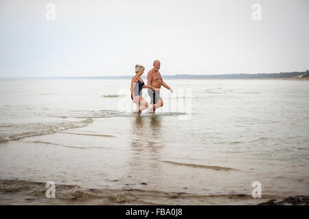 Sweden, Skane, Ahus, Senior couple wading in water - Stock Photo