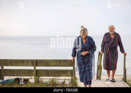 Sweden, Skane, Ahus, Senior couple coming back from beach in bathrobes - Stock Photo