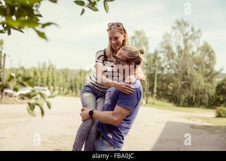 Sweden, Skane, Ostra Goinge, Man carrying girlfriend - Stock Photo