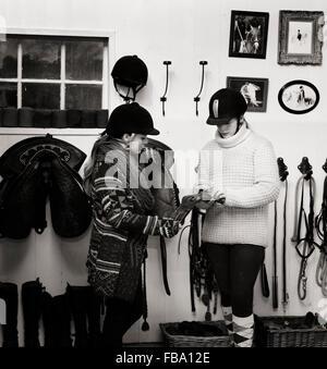 Sweden, Teenage girl (14-15) and woman preparing saddle - Stock Photo