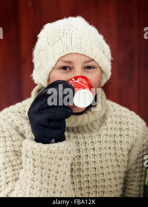 Sweden, Portrait of teenage girl (14-15) drinking coffee cup - Stock Photo