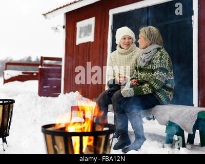 Sweden, Mother talking with teenage girl (14-15) on bench in winter - Stock Photo