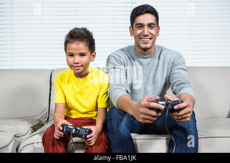 Father and son playing video games on the sofa - Stock Photo