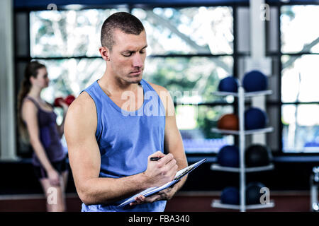 Muscular trainer writing on clipboard - Stock Photo