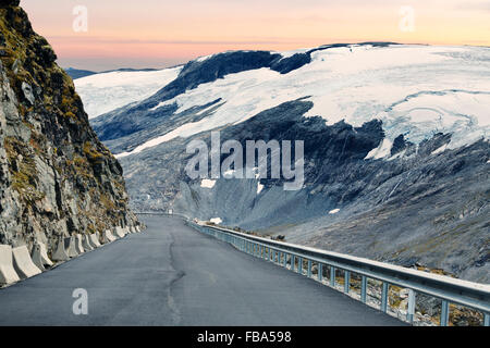 Norway, More og Romsdal, Sunnmore, Geirangerfjord, View down road leading along snowy mountain - Stock Photo
