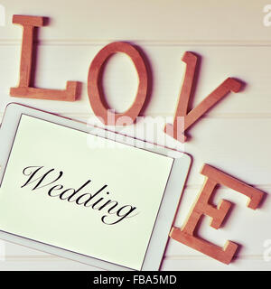some wooden three-dimensional letters forming the word love and a tablet computer with the word wedding in its screen - Stock Photo